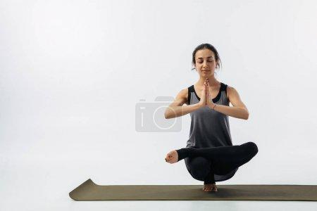 Photo pour Femme pratiquant stand orteil sur tapis de yoga isolé sur blanc - image libre de droit