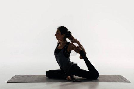 Photo pour Vue de côté de femme pratique l'yoga et le faire roi pigeon blanc - image libre de droit