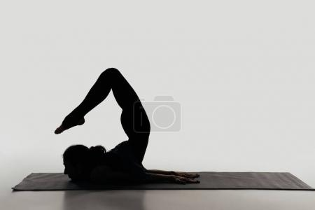 side view of woman practicing yoga on white