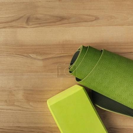 top view of green yoga mat on wooden floor