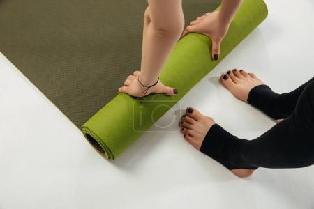 cropped image of woman putting yoga mat on floor to practice yoga