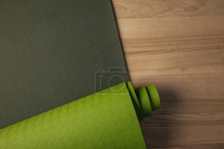 top view of green yoga mat on brown floor