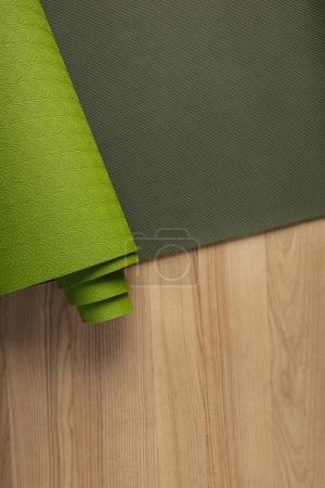 top view of green yoga mat on wooden brown floor