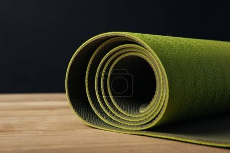 green rolled yoga mat on wooden tabletop on black