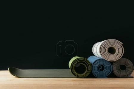 different colored rolled yoga mats on wooden table