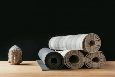 different rolled yoga mats and sculpture of buddha on wooden table