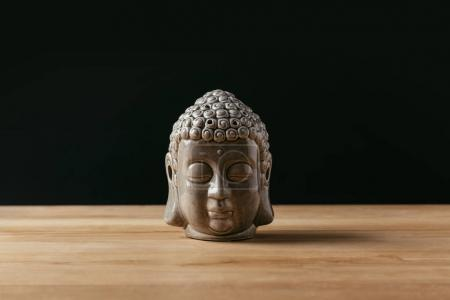 Sculpture of buddha head on wooden tabletop