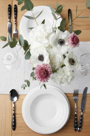 Festive table with cutlery and plates on table with flowers