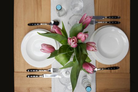 Photo pour Vaisselle avec plaques sur table avec des fleurs dans un vase - image libre de droit