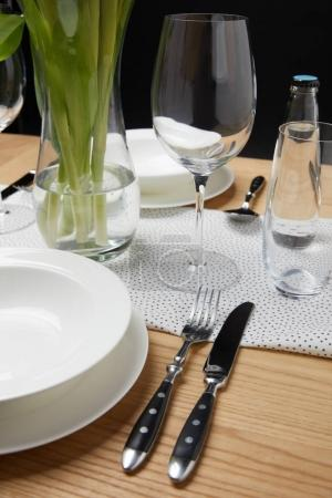 Dinnerware with glasses on table next to bouquet in vase