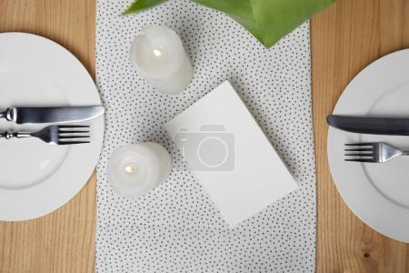 Dinnerware with cutlery on table next to blank card and candles