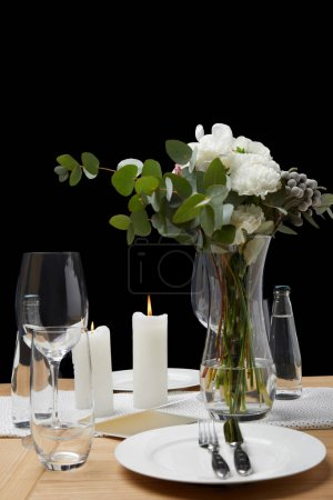 Festive table with cutlery on plates on table with candles on black background