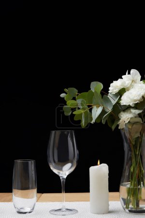 Flowers in vase with empty glasses on table next to candle on black background