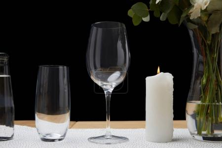 Tender flowers in vase with water bottle and empty glasses on table next to candle on black background