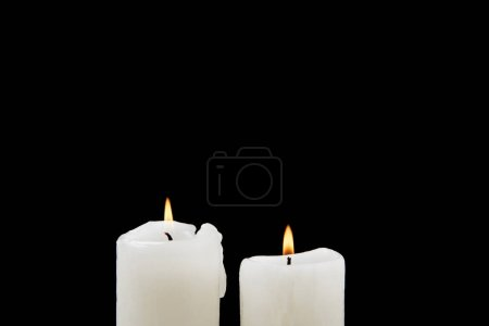 Large burning candles isolated on black