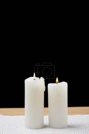 Table with burning candles on black background