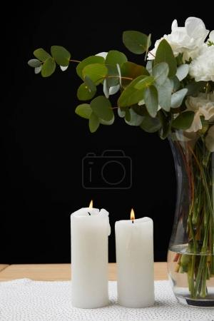 Vase with flower bouquet and candles on table on black background