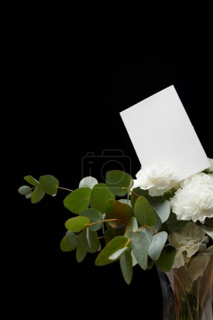 Vase with flower bouquet and empty card isolated on black