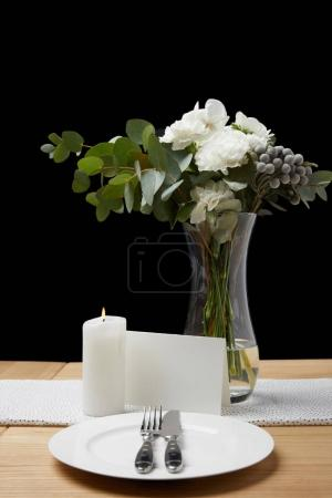 Flowers in vase with cutlery and plate on table next to blank card on black background
