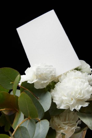 Empty card in flower bouquet isolated on black