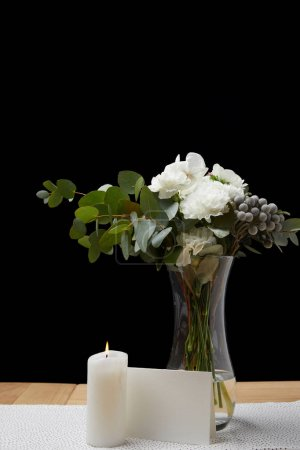 Tender flowers in vase with burning candle on table next to blank card on black background
