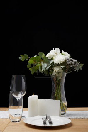 Dinnerware with glasses on table next to blank card and bouquet in vase on black background