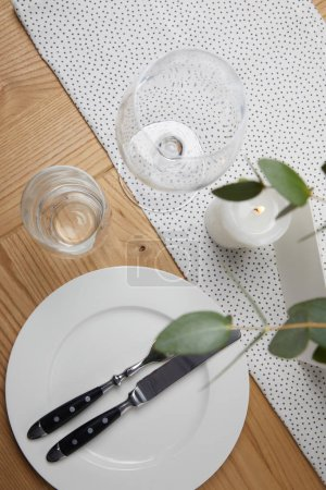 Festive table with cutlery on plate on table with candle