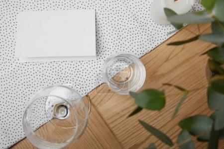Table setting with glasses on table next to blank card and flowers