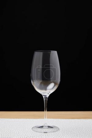 Empty wine glass on table on black background
