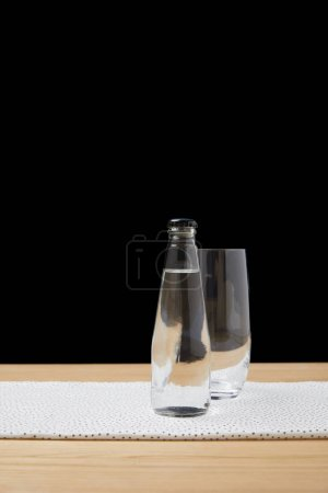 Bottle with water and empty glass on table on black background