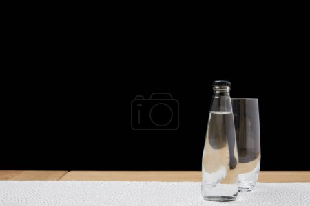 Empty glass and bottle with water on tablecloth on black background