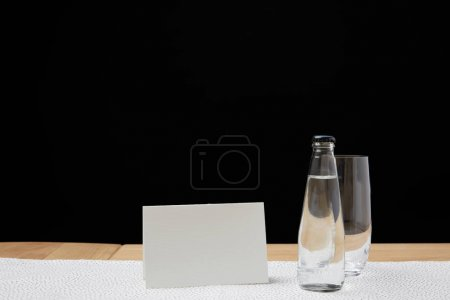 Bottle with water and empty glass on table next to blank card on black background