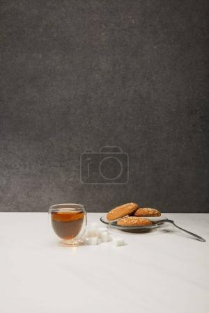 glass cup with fresh hot tea and tasty oatmeal cookies on grey