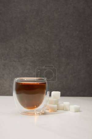 close-up view of glass cup with fresh organic herbal tea and sugar cubes on grey