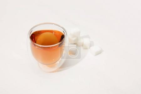 close-up view of glass cup with fresh herbal tea and sugar cubes on grey
