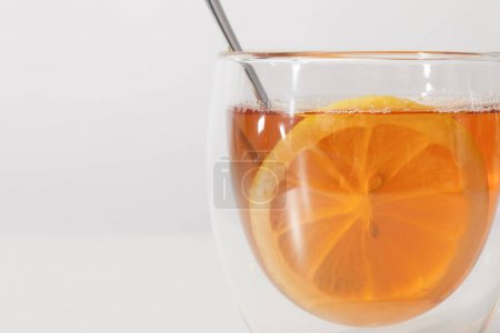 close-up view of glass cup with fresh hot tea, spoon and slice of lemon on grey