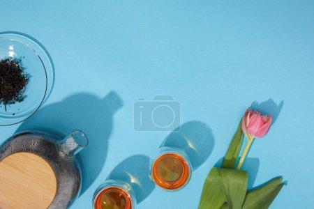 vista superior de dulce té caliente en tazas y tetera y hermoso tulipán flor en azul