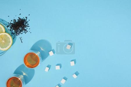 top view of fresh tea in cups, sugar cubes, dry herbal tea and sliced lemon on blue