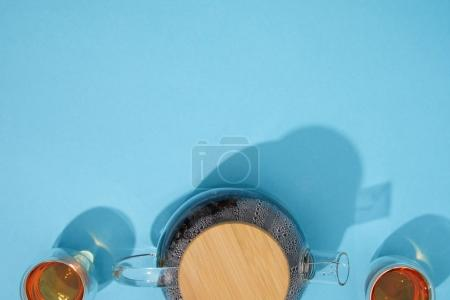 top view of teapot and cups with fresh hot tea on blue