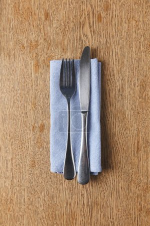 Fork and knife on napkin on wooden table