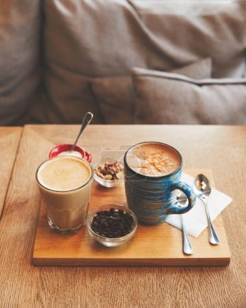Hot coffee drinks in glass and cup with beans and nuts