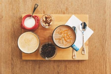 Coffee drinks with walnuts on table in cafe