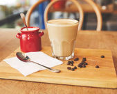 Coffee drink with beans on wooden board