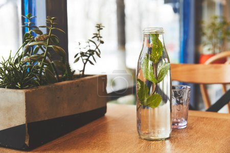 Bottle with mint water and glass on table