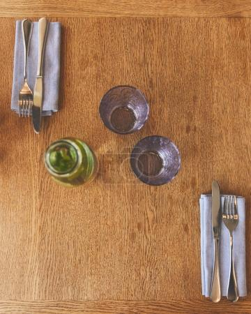 Empty glasses by bottle with mint water and cutlery on table