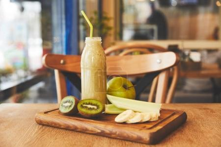 Fruits and smoothie in bottle on table in cafe