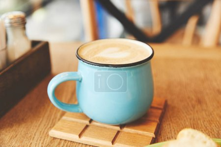 Hot cappuccino in blue mug on table