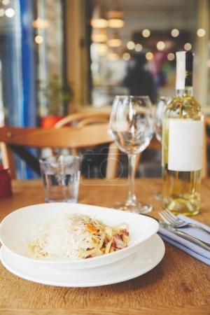 Hot Italian pasta with yolk and cheese served with wine