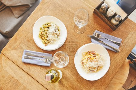 Dinner with Italian pasta in plates served with wine
