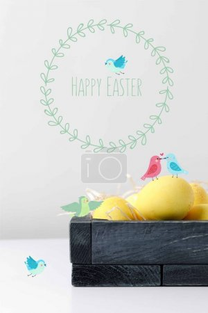 yellow painted easter eggs in wooden box with drawn birds and happy easter lettering on white table